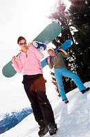 Two young women carrying snowboards