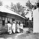 Mahatma Gandhi and others in front of a house in a riot stricken village in Noakhali East Bengal , November 1946 , India NO MR