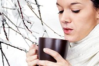 Young woman with hot beverage over snow and ice