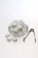 Sugar cubes in a glass bowl with tongs
