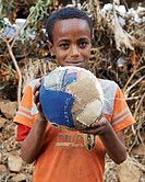 A child holding a homemade football or soccer ball