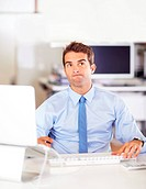 Young businessman looking thoughtful while sitting at his computer