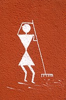 Girl cleaning grass ; Warli painting on wall ; tribal art at top of Parvati hill ; Pune ; Maharashtra ; India
