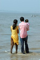 Couple with child in arm enjoying in water of Arabian sea at Juhu beach , Bombay Mumbai , Maharashtra , India No MR