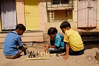 School children play game of chess during their vacations outside their homes in Bombay Mumbai ; Maharashtra ; India