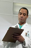 Low angle view of a young male doctor writing on a clipboard