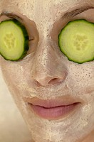 Woman with cucumbers over her eyes and a facial mask on