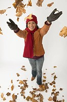 Mature Woman Throwing Autumn Leaves