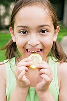 Girl licking a lemon slice