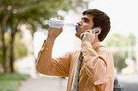 Businessman Drinking Water and Using Cell Phone