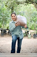 Woman Carrying Bag of Soil