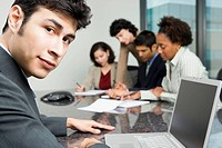 Businessman Sitting at Conference Table with Co_workers