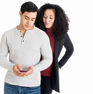 Studio shot of young couple looking at cell phone