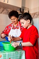 Grandson and grandmother making cookies