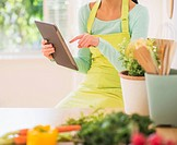 Teenage girl using digital tablet in kitchen