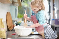 Girl mixing dough in kitchen