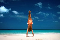Man doing handstand on tropical beach