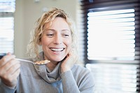 Smiling woman eating cereal indoors