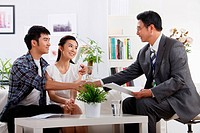 Businessman shaking hands with young couple at home