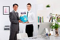 Two businessmen holding a world globe
