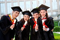 Four university students in graduation gown