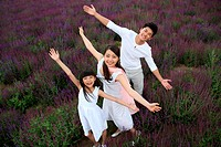Oriental family standing in lavender garden opening arms