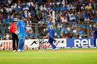 Sri Lankan bowler Lasith Malinga bowls while Indian batsman M S Dhoni looks on during the 2011 ICC World Cup Final between India and Sri Lanka at Wank...