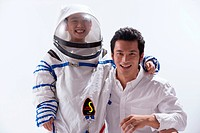Boy in spacesuit standing with young man