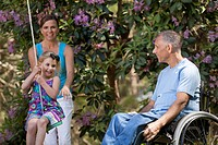 Man with spinal cord injury in wheelchair watching his daughter on swing along with wife