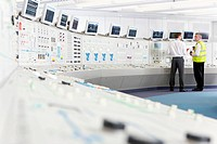 Engineers at control panel in control room of nuclear power station
