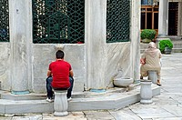 Man in modern dress and woman in traditional dress at the water taps, Blue Mosque, Istanbul, Turkey, NMR