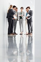 Business people with paperwork meeting in corridor
