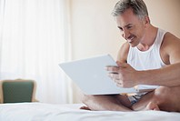Smiling man using laptop in bed
