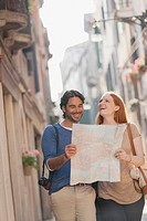 Smiling couple walking with map on narrow street in Venice