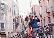 Smiling couple taking photograph in Venice