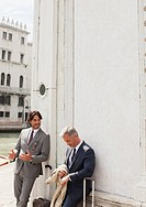 Businessmen with suitcases talking and leaning against building in Venice