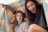 Enthusiastic mother and daughter under blanket