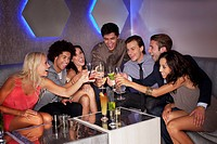 Friends toasting cocktails in nightclub
