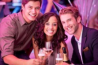Portrait of smiling friends drinking champagne in nightclub