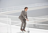 Businessman riding scooter down walkway