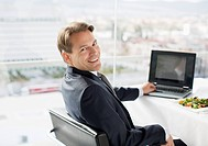 Portrait of smiling businessman with laptop and lunch