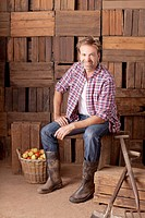 Portrait of smiling man sitting next to bushel of apples