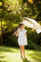 Girl carrying butterfly net in grass