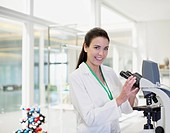 Portrait of confident scientist using microscope in laboratory
