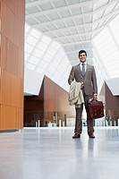 Portrait of smiling businessman holding coat and briefcase in lobby