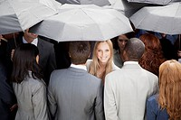 Portrait of smiling businesswoman surrounded by crowd with umbrellas
