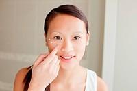 Woman applying moisturizer in bathroom