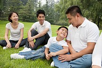 Chinese family sitting on grass in park