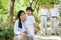 Chinese mother and son smiling in park