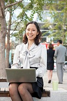 Chinese businesswoman using laptop outdoors